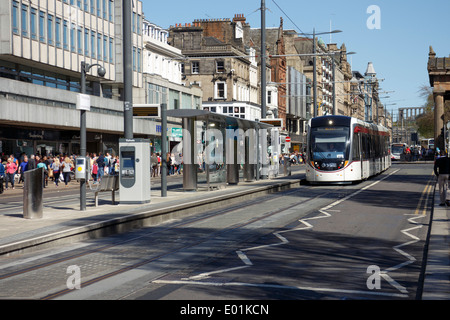 Prince Street scene with approaching tram during testing on a bright busy Sunday afternoon. Tram stop in the foreground. - Stock Photo