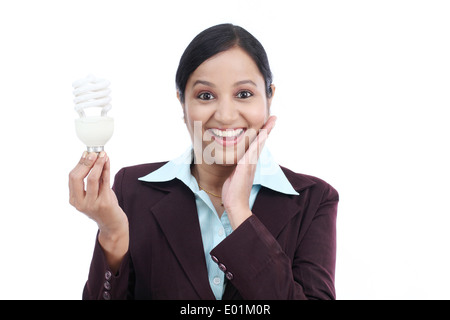 Young Indian business woman holding bulb against white background - Stock Photo