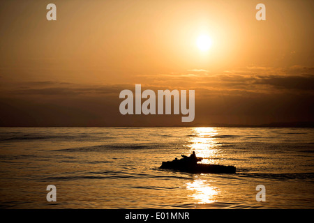 A US Marine Corps amphibious assault vehicle maneuvers through the water at sunset during a splash and recovery - Stock Photo