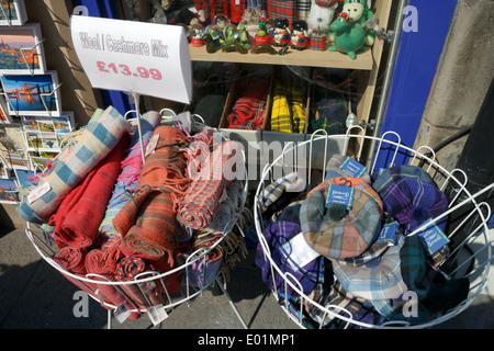 Wool and cashmere blend tartan scarves and hats on display in front of a tourist store on the Royal Mile, Edinburgh. - Stock Photo