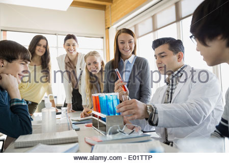 High school students and teacher conducting scientific experiment - Stock Photo