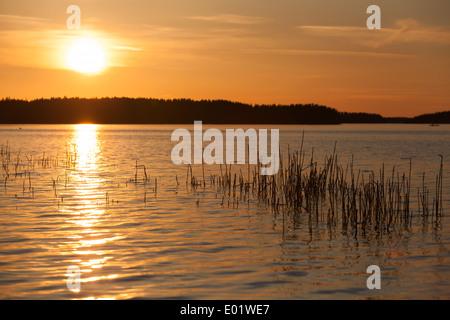 Orange sunset on Saimaa lake in Finland - Stock Photo