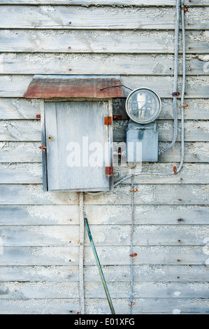 Domestic electricity meter on the exterior wall of an old abandoned house. - Stock Photo
