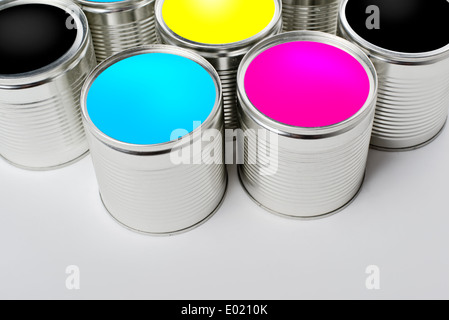 CMYK color paint tin cans opened top view. Cyan, Magenta, Yellow and Black colors are basic for printing industry. - Stock Photo