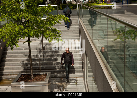 Man walking down steps as man walks up steps in a city - Stock Photo