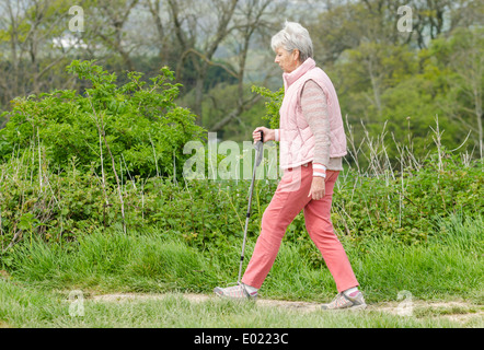Elderly lady with a stick walking in the countryside. - Stock Photo