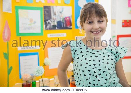 Portrait of confident school girl at science fair - Stock Photo