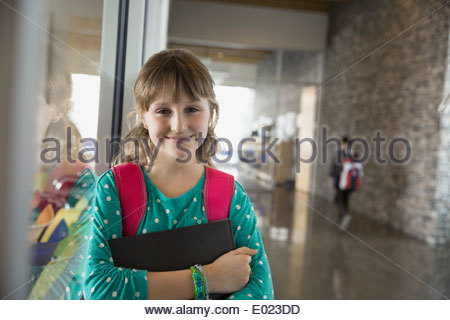 Portrait of confident school girl in corridor - Stock Photo