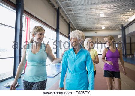 Smiling women walking on gym track - Stock Photo