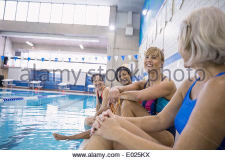 Women talking at indoor swimming pool - Stock Photo