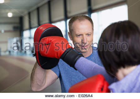 Woman boxing with personal trainer - Stock Photo