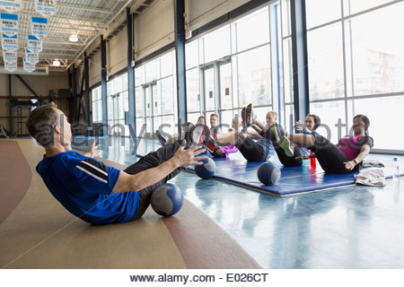Instructor guiding exercise class at gym - Stock Photo