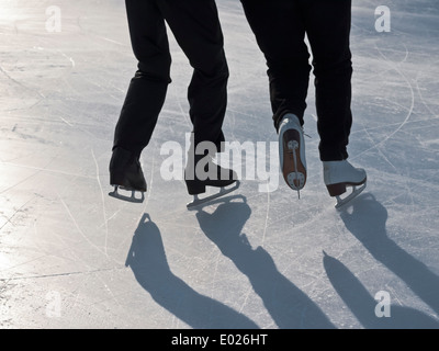 details of figure skaters on ice rink in the bright winter backlight - Stock Photo