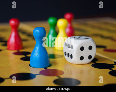Close up of colorful wooden pins and dices on a classic board game - Stock Photo