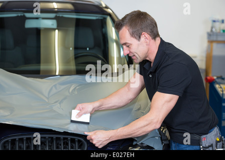 Car wrappers using squeegee to straighten vinyl foil  - Stock Photo