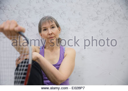 Portrait of serious woman holding racket - Stock Photo