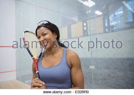 Smiling woman holding squash racket - Stock Photo