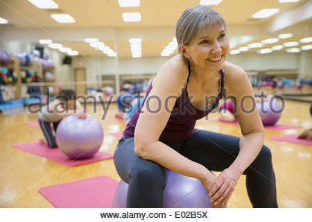 Smiling woman on fitness ball in exercise class - Stock Photo
