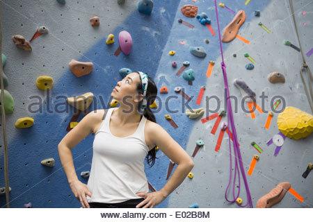 Woman standing below rock climbing wall - Stock Photo