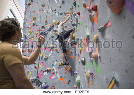 Man watching woman climb indoor rock wall - Stock Photo