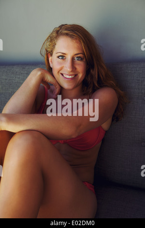 Portrait of an attractive young woman wearing red bikini sitting on a couch smiling at camera. - Stock Photo