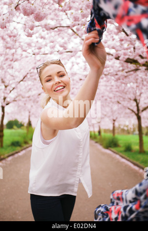 Beautiful woman playing with scarf at spring blossom garden. Carefree young female enjoying herself at park during - Stock Photo