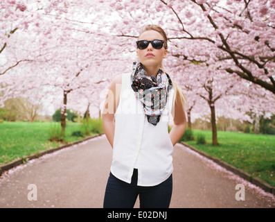Fashionable young lady posing confidently at park. Attractive female model at spring blossom park - Stock Photo