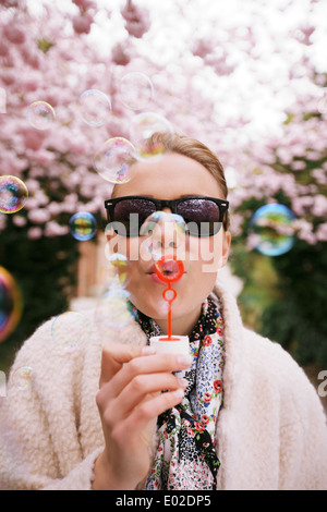 Cute young female wearing sunglasses blowing bubbles at spring park. Beautiful caucasian woman blowing soap bubbles. - Stock Photo