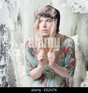 Blonde woman in front of ice covered mountain wearing summer dress and winter hat - Stock Photo
