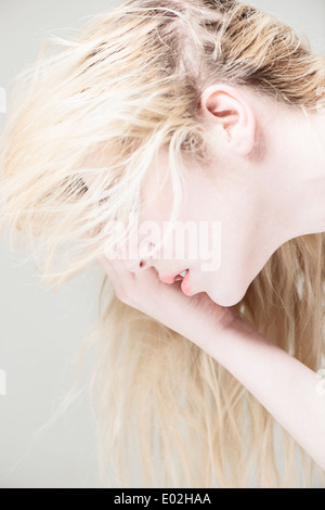 Side view of young beautiful blonde woman with long hair. Looking down, covering face with hand. - Stock Photo