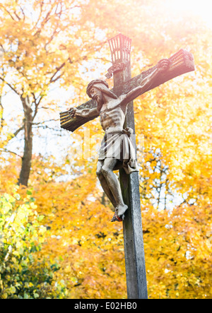 Jesus Christ on the cross with fall trees in the background. Cemetery in Stockholm, Sweden. - Stock Photo