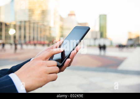 Female Mobile phone hand outdoor message sms e-mail - Stock Photo