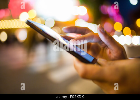 Female Cell phone close-up hand outdoor message sms e-mail - Stock Photo