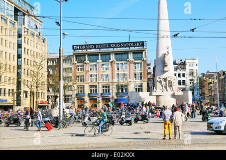 People relaxing in Dam Square outside NH Grand Hotel Krasnapolsky, Amsterdam, Netherlands - Stock Photo