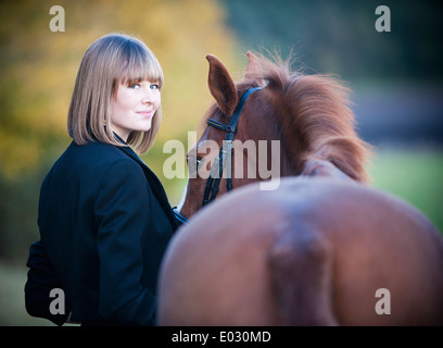 A woman leading a bay horse by the bridle. - Stock Photo