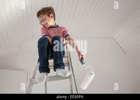 A boy seated on a stepladder. - Stock Photo