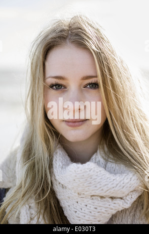 A young girl with blonde hair looking at the camera. - Stock Photo