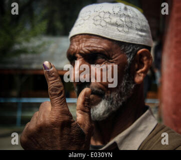 Zawalpora, India. 30th Apr, 2014. A man shows her inked finger after casting her ballot at a polling station near - Stock Photo