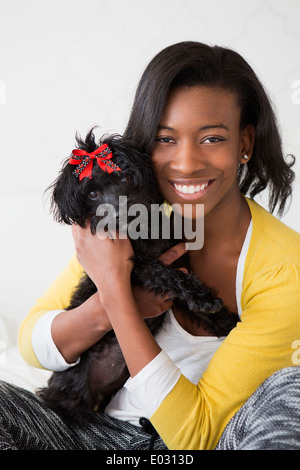 A young girl smiling holding her small black pet dog. - Stock Photo