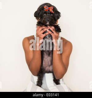 A young girl holding her small black pet dog. - Stock Photo