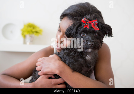 A young girl hugging her small black pet dog. - Stock Photo