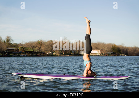 A woman doing a headstand on a paddle board on lake