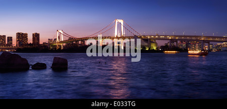 Beautiful panoramic scenery of the Rainbow bridge across Tokyo Bay at nighttime. Odaiba, Tokyo, Japan. - Stock Photo