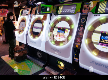 Person playing MaiMai rhythm game slot machine at an arcade in Tokyo, Japan - Stock Photo