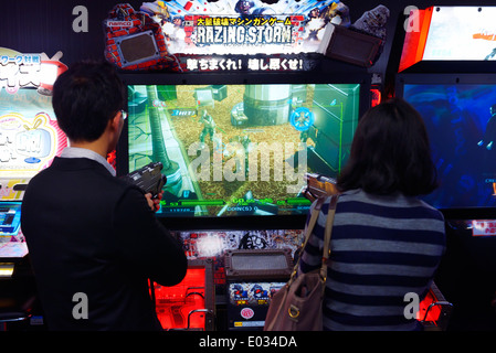 People playing Razing Storm shooting video game arcade slot machines in Tokyo, Japan - Stock Photo