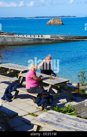 Cheers as visitors enjoy a drink outside the Turks Head Pub at St Agnes, Isles of Scilly, Scillies, Cornwall in - Stock Photo