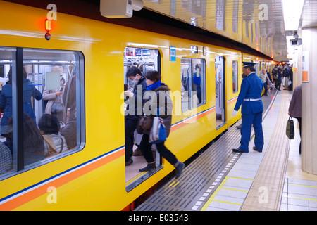 People entering Tokyo Metro subway train on a platform. Tokyo, Japan. - Stock Photo
