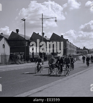 1950s. Historical picture, a group of steel workers on bikes going to the British motoring factory, in Cowley, Oxford, - Stock Photo