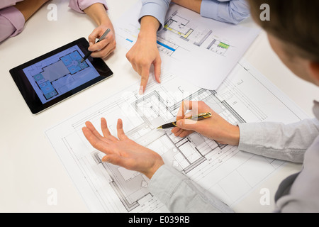 Team architects working on blueprints construction project in office - Stock Photo