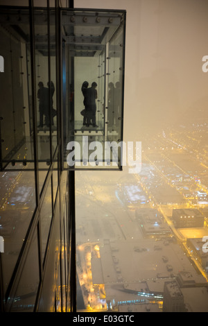 People enjoy the nighttime view from the Ledge in the Willis Tower in Chicago. - Stock Photo